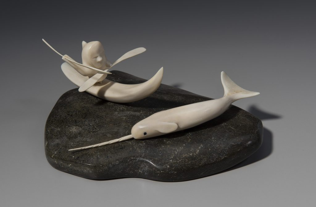 Sculpture of a person hunting a narwhal by kayak
