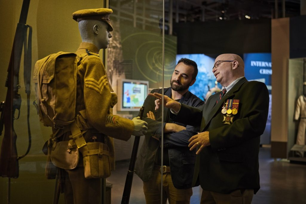 Visitors looking at a uniform in War Museum Gallery