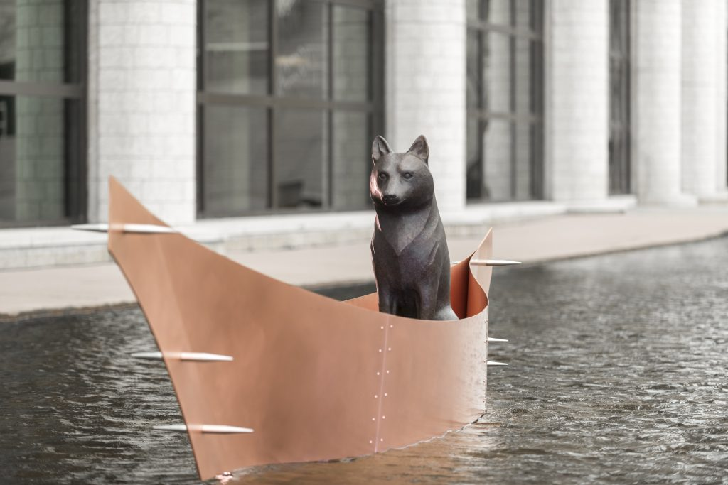 Life size sculpture of a wolf in a canoe