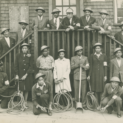 A group of male and female African Canadian volunteers pose with Mark II helmets and hoses.