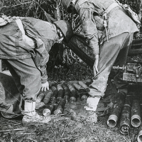 Two soldiers bending over to stack ammunition.
