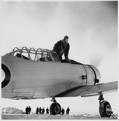 A pilot stands in the cockpit, looking out over the wing of an airplane.