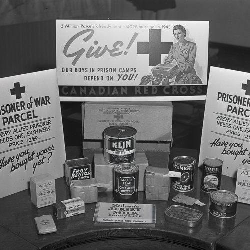 An unpacked Red Cross parcel shows an assortment of items, including canned foods and soap.