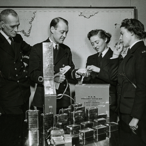 Two male and two female naval members unwrap and taste the chocolate ration from life boat ration box.