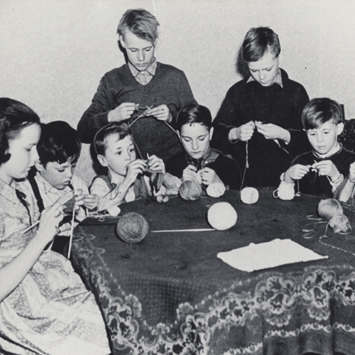 Eight boys and one girl sit around a table knitting.