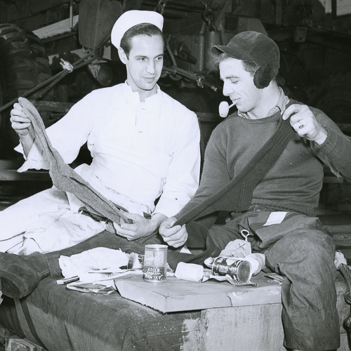 Two sailors sitting together hold up hand-knit socks.