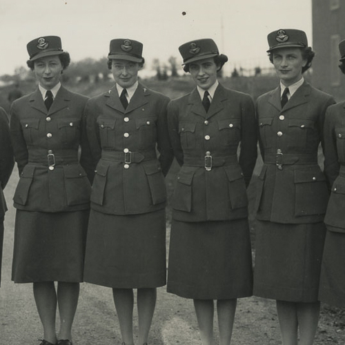 Seven members of the RCAF Women's Division stand in a row, in dress uniform.