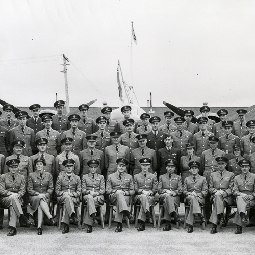 Sixty officers are arranged in rows for a group portrait. There are three women present in the group.