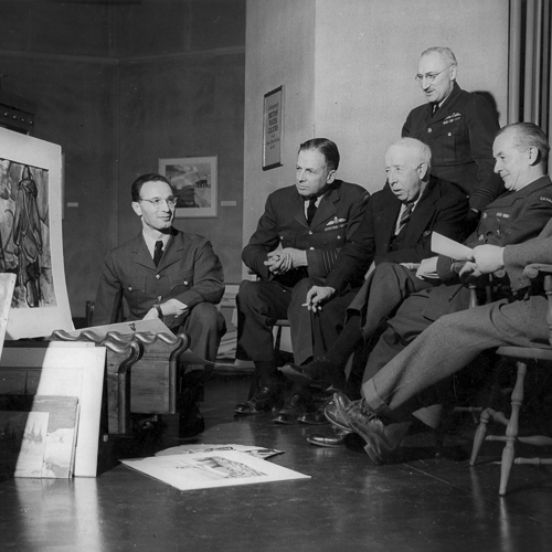 Seven men gathered in front of several finished works of art.