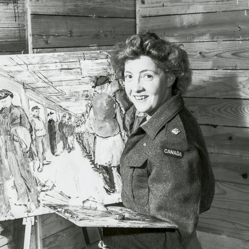 Molly Lamb Bobak, poses in her studio in front of a painting, in uniform and holding a palette.