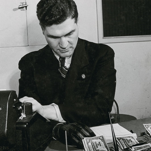 A man in a suit counts money on his desk. His prosthetic right hand rests in front of him.