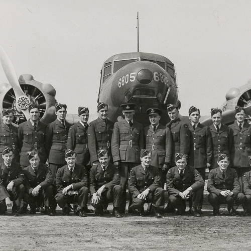 Large group photo of aviators in dress uniforms in front of a plane.