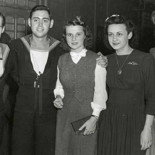 Two sailors in uniform pose with three young civilian women.