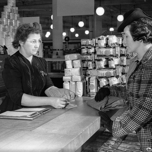 A woman uses ration coupons to purchase food from a female clerk.