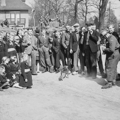 A soldier photographs a group of Dutch children. Several civilians stand nearby.