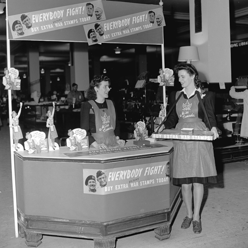 Two women in Miss Canada aprons at a War Savings Stamps kiosk.