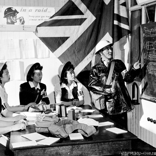 Five Chinese Canadian women wearing A.R.P. armbands being taught about bombs.