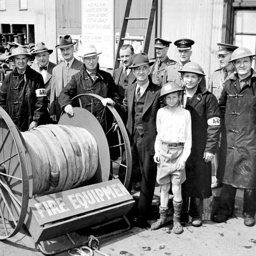 Shipyard workers and a young boy pose by a firehose.