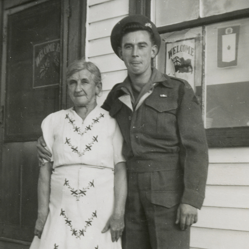 A soldier and his mother outside their home.