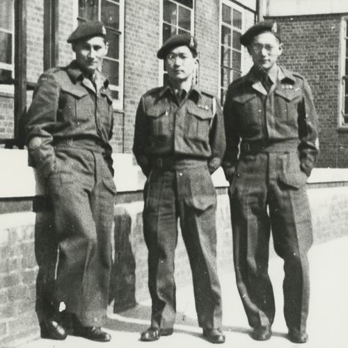 Three male Japanese Canadian language instructors in army uniforms outside their school.