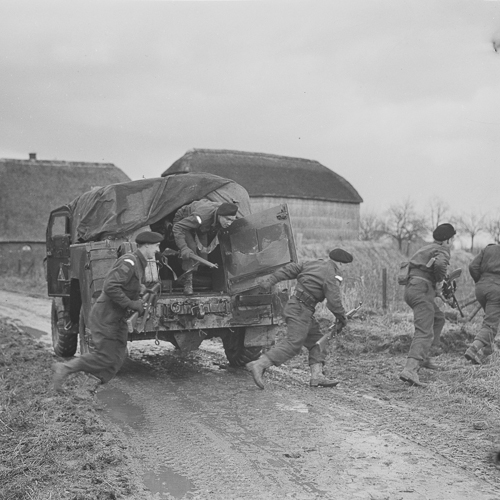 Canadian Soldiers jump out of an armoured truck.
