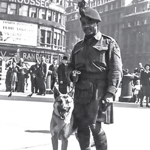 An African Canadian soldier in a battle dress jacket and kilt stands with his dog on a street in London.