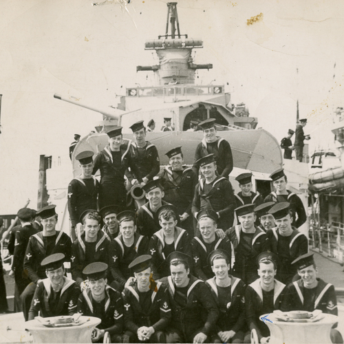 A group of sailors on a ship wearing their caps at different angles.