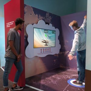 A young man uses his body to navigate a virtual airplane while his friend watches.