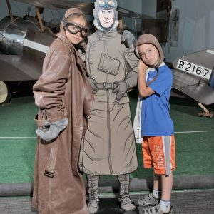 Two kids dress up as pilots and pose with a cutout of a cartoon pilot.