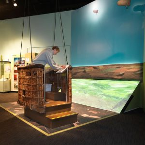 A young man interacting with an exhibition interactive