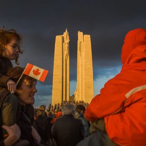 Two children sit atop the shoulders of adults as the Vimy monument stands, lit by the sun, in the background