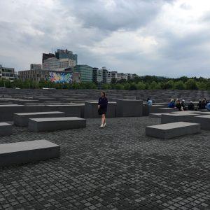 A girl walks among a field of large, grey stone blocks