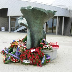 A stylized memorial statue with wreaths, flowers and poppies laid at its base..