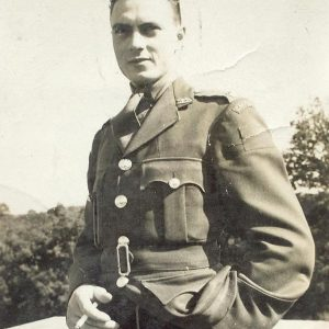 A black and white photograph of a man in uniform holding a cigarette and looking at the camera