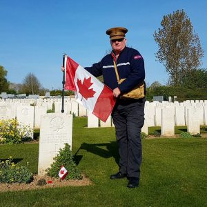 A man with a Canadian flag in a cemetery