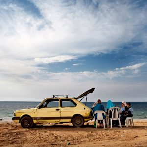 Family with car on beach