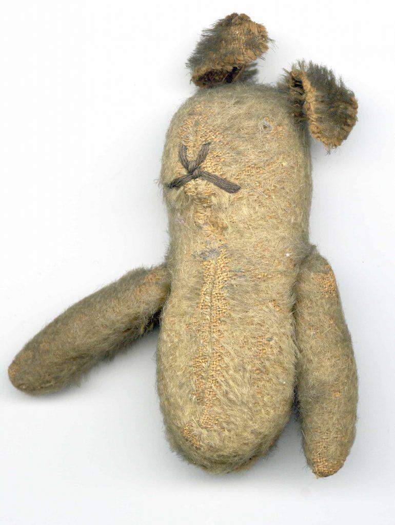 A teddy bear missing its legs