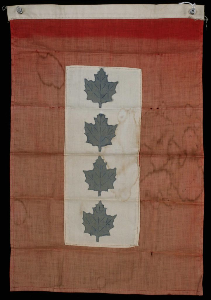 A faded red flag, with a central white patch adorned with four blue maple leaves