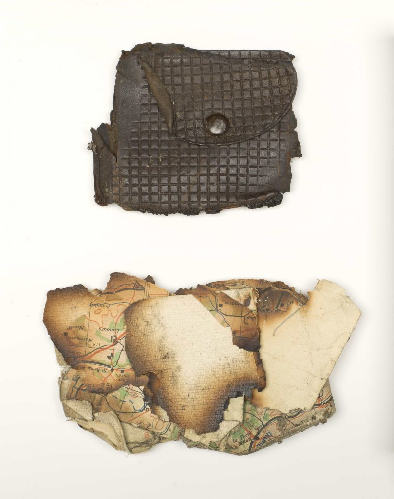 A damaged change purse and pieces of a charred map