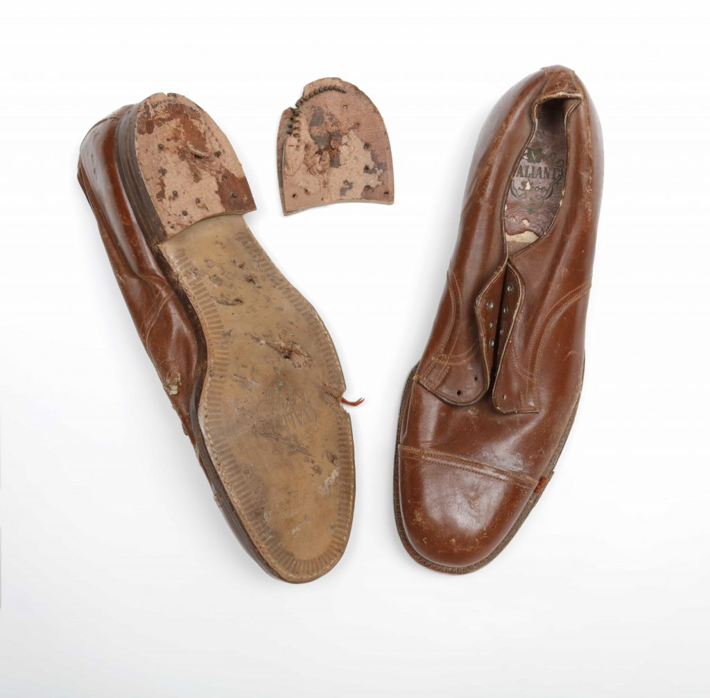 Two brown leather shoes, one of which is upside down, showing a damaged sole and detached heel