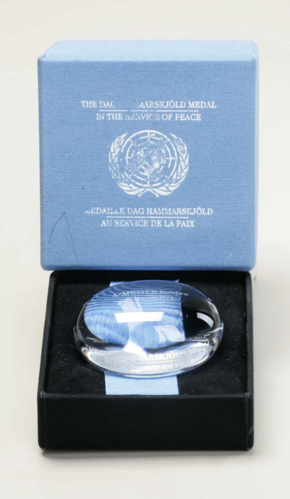 A clear crystal glass object in for the shape of a gently flattened sphere, with engraving, in a display box with the words 'The Dag Hammarskjöld Medal/In the Service of Peace/Médaille Dag Hammarskjöld/Au service de la paix' printed on the box lid.