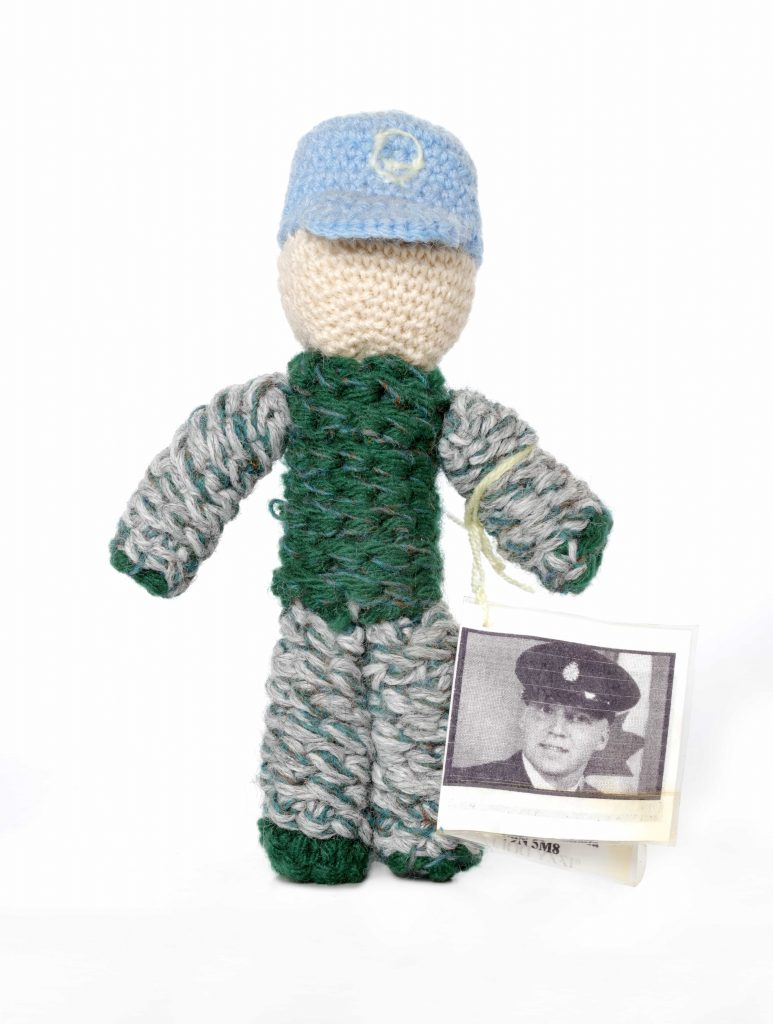 A knit doll wearing a light blue cap and green camouflage-style clothing. Attached to its arm is a tag showing the face of a uniformed man.