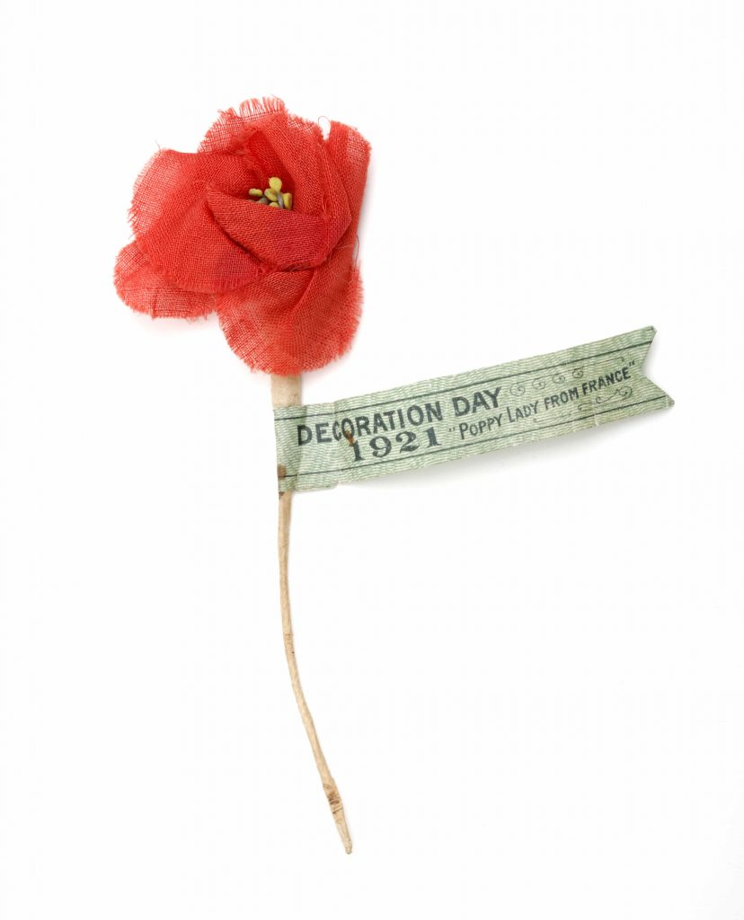 A fabric poppy on a wire stem, with a tag