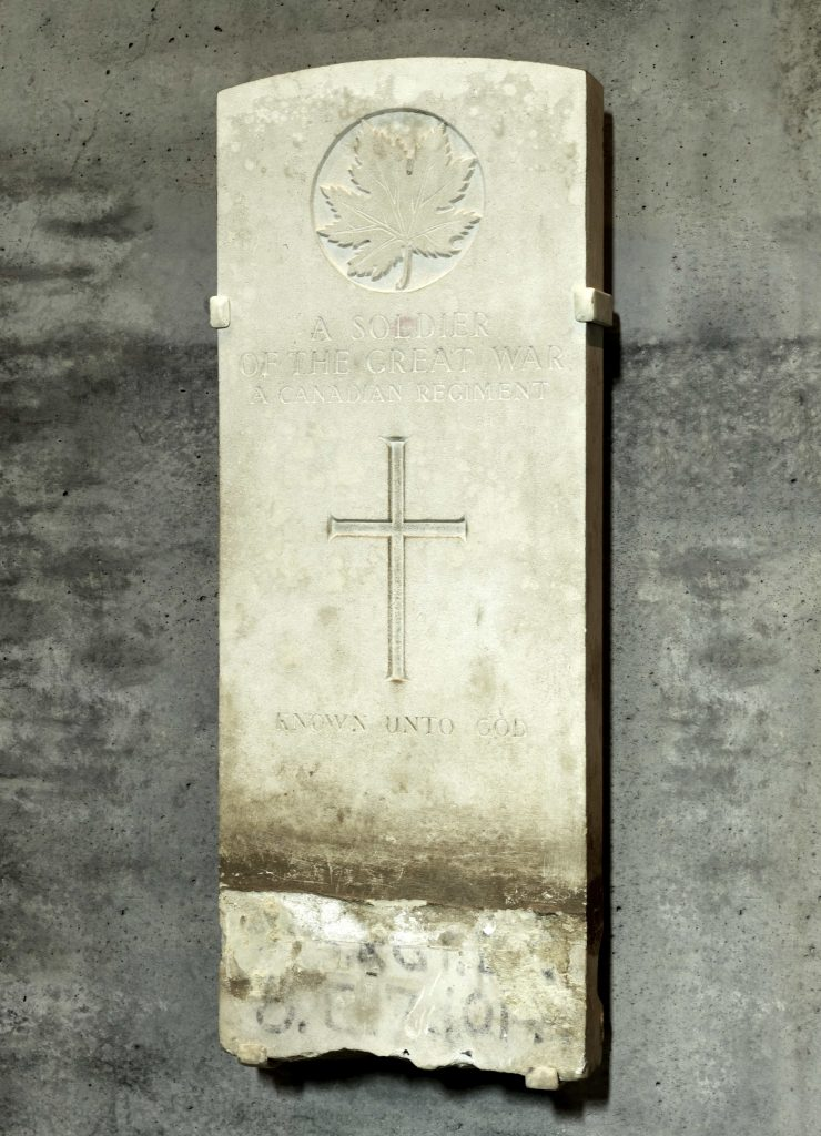 A stone tombstone decorated with a maple leaf and a cross, and the inscription: A Soldier of the Great War - A Canadian Regiment - Known Unto God