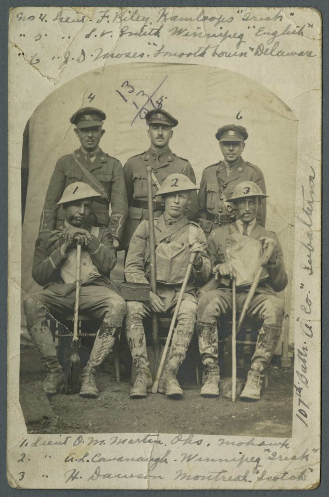 Three uniformed men stand behind three seated men wearing mud-stained uniforms and holding shovels and walking sticks. The men have been identified with numbers and accompanying text.