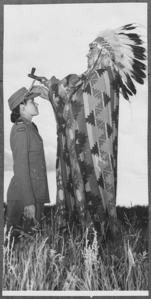 A uniformed Indigenous woman kneels in a field before an Indigenous man with mismatched ceremonial clothing and items.