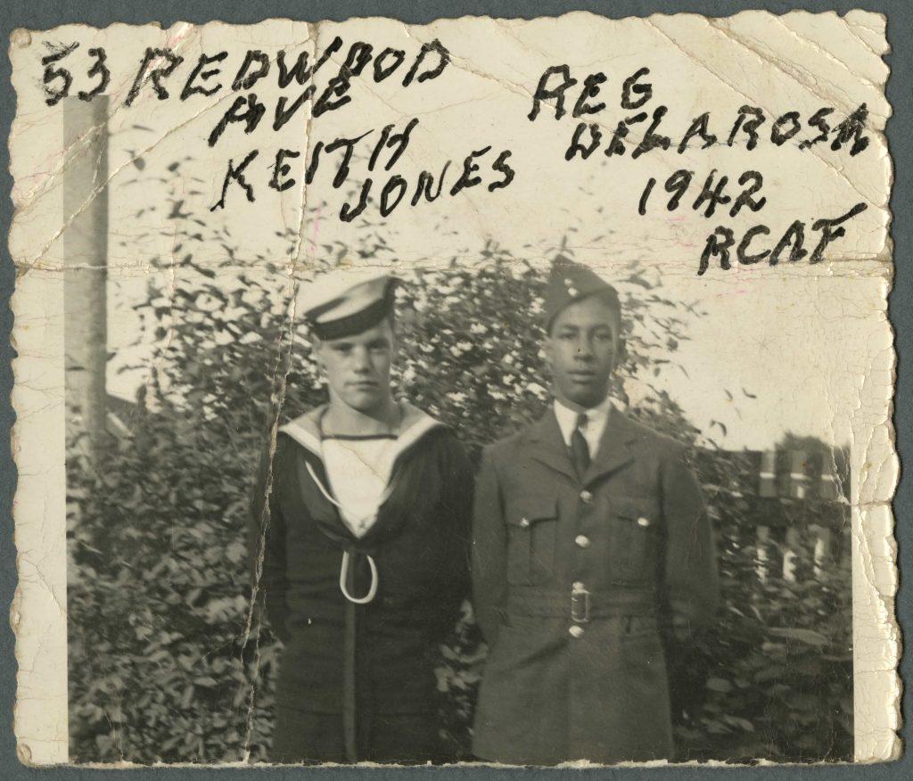 A white man in a navy uniform stands beside a Black man in an air force uniform. Handwritten text identifies the men.