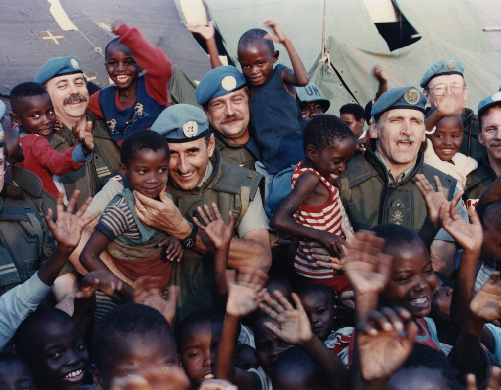 A crowd of smiling Black children and white men wearing Peacekeeping uniforms smile and wave for the camera