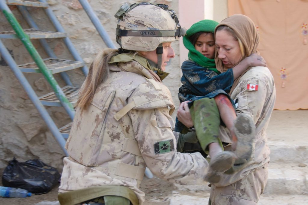 A uniformed woman carries an Afghan child in her arms, while another uniformed woman assists.